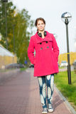 Beautiful woman in red coat walking autumn street Stock Images