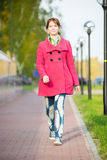 Beautiful woman in red coat walking autumn street Stock Image
