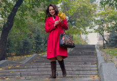 Beautiful woman in a red coat walking down the stairs Royalty Free Stock Photos