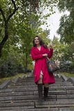 Beautiful woman in a red coat walking down the stairs Stock Photo