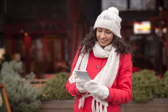 Beautiful woman in red coat and wool cap and gloves with smartph Royalty Free Stock Photo