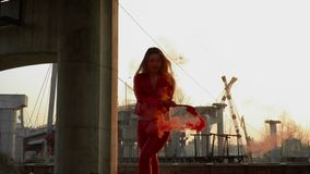 Beautiful woman in red costume dancing with red smoke near abandoned bridge. Beautiful woman wearing red costume is dancing at the sunset background with red stock footage