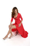 Beautiful Woman In Red Dress 2. Beautiful woman in a long red dress sitting on a stool Stock Photo
