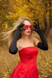 Beautiful woman  in red dress. In autumn day Royalty Free Stock Photography