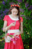 Beautiful woman in a red dress with basket of flowers Royalty Free Stock Photography
