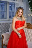 Beautiful woman in a red dress with a crown on her head royalty free stock photo