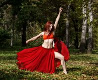 Redhead beautiful woman in red dress dancing in a autumn forest. Royalty Free Stock Photography