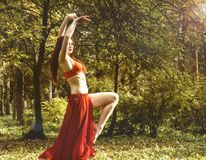 Redhead beautiful woman in red dress dancing in a autumn forest. Royalty Free Stock Images