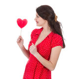 Beautiful woman in red dress eagers a red heart-shaped lollipop Royalty Free Stock Photography