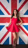 Beautiful woman in the red dress in front of the British flag Stock Photos