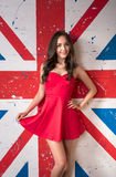 Beautiful woman in the red dress in front of the British flag Royalty Free Stock Images