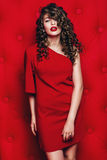 Beautiful woman in red dress with long curls Royalty Free Stock Photography