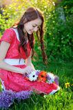 Beautiful woman in red dress makes a wreath of flowers Royalty Free Stock Image