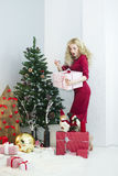 Beautiful woman in a red dress with many gift boxes Stock Images