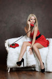 The beautiful woman in a red dress with old phone. The woman in dress with old phone Stock Photo