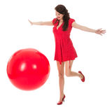 Beautiful woman in red dress playing with a big red balloon royalty free stock photography