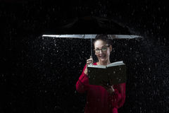 Beautiful woman with red dress reading a book in rain under an u Stock Photography