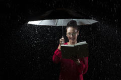 Beautiful woman with red dress reading a book in rain under an u Royalty Free Stock Photography