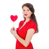 Beautiful woman in red dress with red heart-shaped lollipop Stock Photography