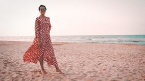 Slowmotion view of a beautiful woman in red dress smiling and looking to the mediterranean sea at sunset. Beautiful woman in red dress and round sunglasses stock footage