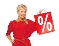 Beautiful woman in red dress with shopping bag Royalty Free Stock Images