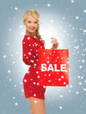 Beautiful woman in red dress with shopping bag Royalty Free Stock Image