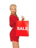 Beautiful woman in red dress with shopping bag Stock Photography
