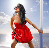 Beautiful woman in red dress on the shore Stock Photo