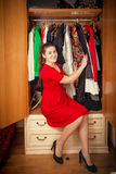 Beautiful woman in red dress sitting at big wardrobe Stock Photo