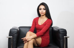 Beautiful woman in red dress sitting on black chair. Beautiful young woman in red dress sitting on black chair Royalty Free Stock Photo