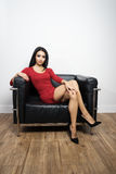 Beautiful woman in red dress sitting on black chair. Beautiful young woman in red dress sitting on black chair Royalty Free Stock Photography
