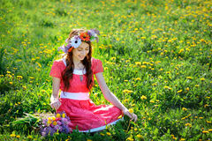 Beautiful woman in red dress sitting on the grass with a branch of lilac Stock Images