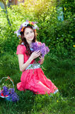 Beautiful woman in red dress sitting on the grass with a branch of lilac Royalty Free Stock Photography
