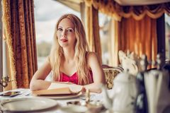 Woman in red dress at expensive restaurant Stock Photography
