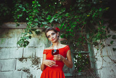 Beautiful woman in red dress standing with glass of wine in the. Young beautiful woman in red dress standing with glass of wine in the hands near the old Royalty Free Stock Image