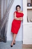 Beautiful woman in red dress standing on stairs against white wall Royalty Free Stock Photography