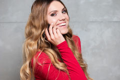 Beautiful woman in red dress talks on mobile phone Stock Images