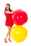 Beautiful woman in red dress with two big red and yellow balloons royalty free stock photo