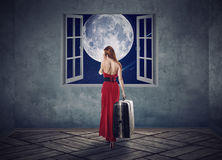 Beautiful woman in red dress walking to opened window with moon Royalty Free Stock Photography