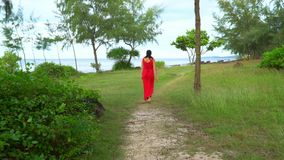 Beautiful Woman in Red Dress Walking in Tropical Garden.. On this video you can see as the woman in a red dress walks on a tropical garden. The woman in a long stock footage