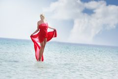 Beautiful woman in red dress walking by water Stock Photography