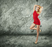 Beautiful Woman in Red Dress on Wall Background Royalty Free Stock Image