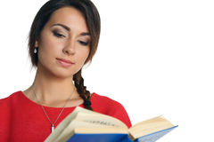 Beautiful woman in red dress wearing plait reading blue book Stock Photo