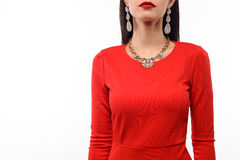Beautiful woman in red evening dress with necklace and earrings. Royalty Free Stock Image