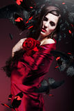 Beautiful woman in red fabric with red rose and butterflies Stock Photo