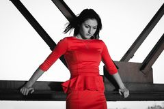Beautiful woman in red fluttering dress. Urban background stock image