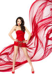 Beautiful woman in red flying dress. Hands on hips. Beautiful woman standing in red flying dress. Hands on hips. Chiffon flutter on a wind flow over white royalty free stock photo