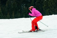 A beautiful woman in red gear learns to ride skiing in the Ukrainian Carpathians royalty free stock photo