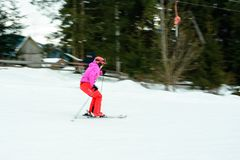 A beautiful woman in red gear learns to ride skiing in the Ukrainian Carpathians royalty free stock photography