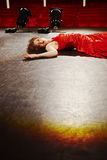 Beautiful Woman In Red Gown Lying On Stage Stock Photo